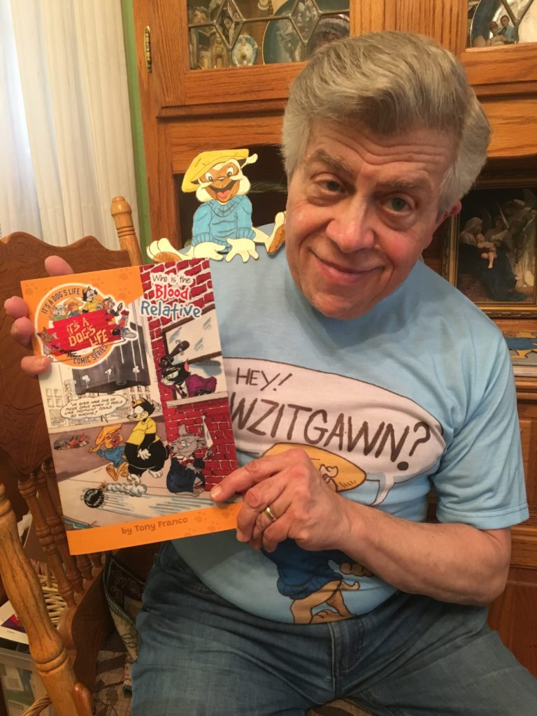Tony Franco comic artist holding his first comic book called Its a dogs life blood relative